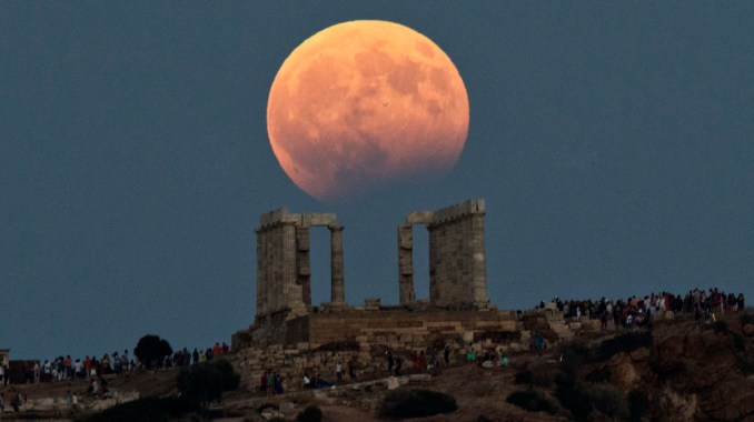 The August full moon rises above the 5th Century BC Temple of Poseidon at Cape Sounio, south of Athens, on Aug. 7, 2017. More than a hundred of Greece's ancient sites _ but not the Acropolis in Athens _ and museums were kept open until late Monday and concerts organized to allow visitors to enjoy the full moon, which is accompanied by a partial lunar eclipse. (AP/Petros Giannakouris)