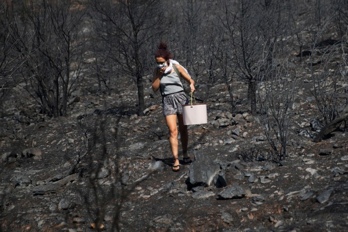 A woman with a bucket walks among burnt forest land during a wildfire near the suburb of Kaisariani in eastern Athens, on, Aug. 10, 2017. (AP/Petros Giannakouris)