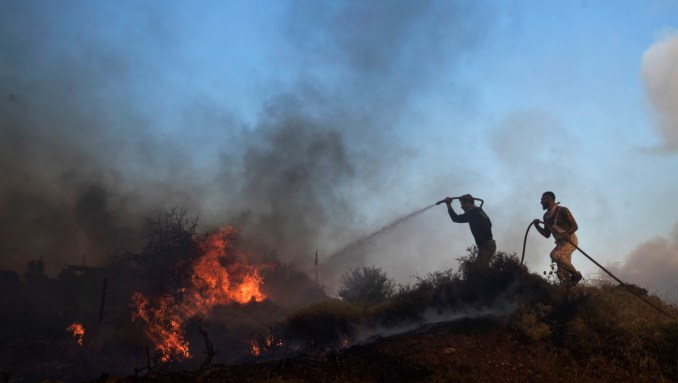 Volunteers try to extinguish the fire outside a military base at the village of Varnava , north of Athens, Aug. 14, 2017. (AP/Petros Giannakouris)