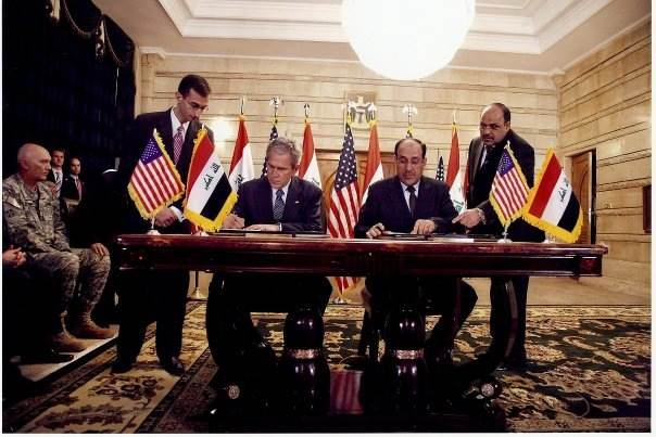 Ali Khedery, pictured far left, watches as U.S. President George W. Bush signs an agreement with Iraqi Prime Minister Nouri al-Maliki. (Photo: Public Domain)