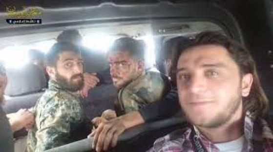 Muawiya Hassan Agha takes a selfie with two captured and condemned SAA soldiers who were later publicly tortured and executed. Agha posted related footage to his Facebook page that was later deleted.
