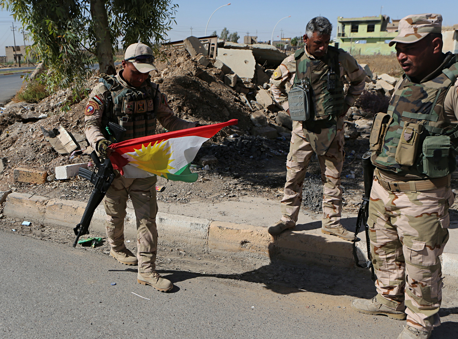 Iraqi soldiers remove a Kurdish flag from a checkpoint in Bashiqa, Iraq, Oct. 18, 2017. Iraqi forces retook control of the town on the northeastern outskirts of Mosul. Kurdish forces pulled out of disputed areas across northern and eastern Iraq a day after handing Kirkuk to federal forces amid a tense standoff following last month's vote for independence. (AP/Khalid Mohammed)