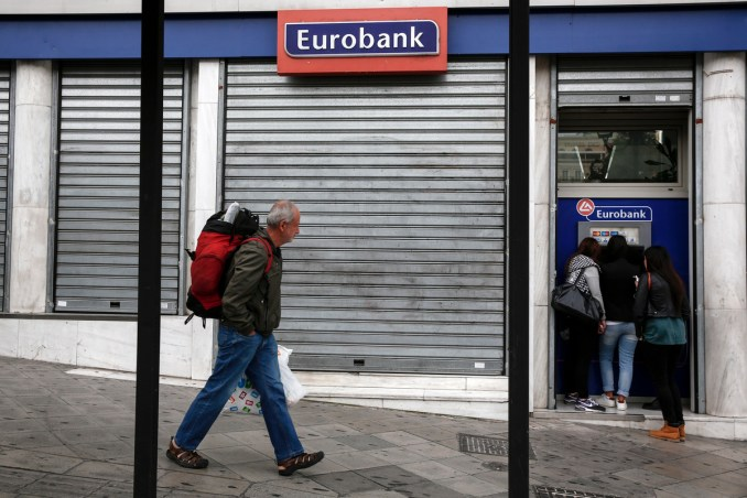 A tourist makes his way as youths make a transaction at an automated teller machine (ATM) of a Eurobank Bank branch in Athens, Saturday, Oct. 31, 2015. The European Central Bank says Greece's battered banks need 14.4 billion euros ($15.8 billion) in fresh money to get back on their feet and resume normal business. (AP Photo/Yorgos Karahalis)