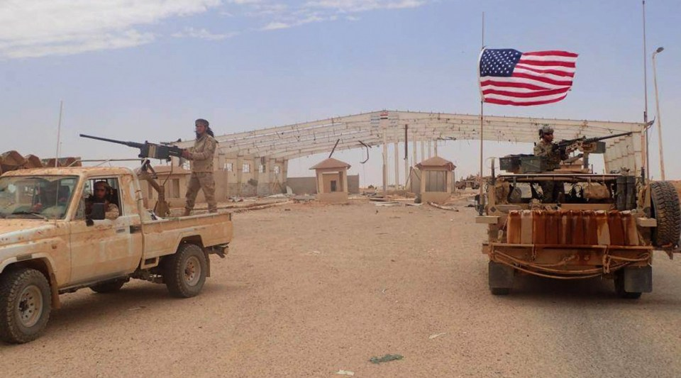 A U.S.-backed anti-government fighter mans a heavy automatic machine gun, left, next to an American soldier as they take their positions at Tanf, a border crossing between Syria and Iraq (Hammurabi's Justice News/AP)