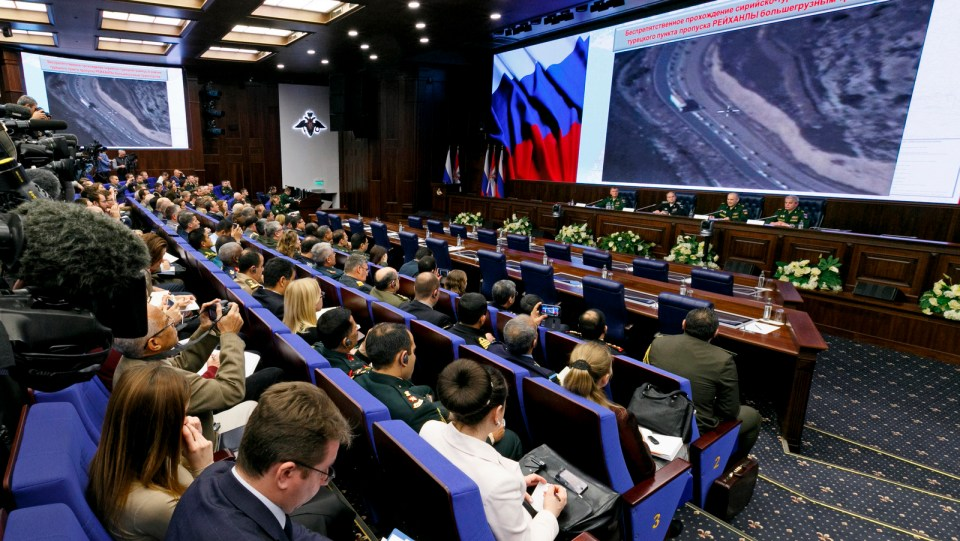 Russian top military officials speak to the media in front of aerial images of oil trucks near Turkey's border with Syria at a briefing in Moscow, Russia, Dec. 2, 2015. (Vadim Savitsky/ Russian Defense Ministry Press Service via AP)