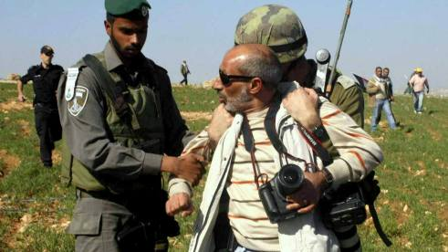 Israeli troops arrest Associated Press photographer Nasser Shiyoukhi while he was covering a protest in Palestinian West Bank town of Yatta. AP Photo