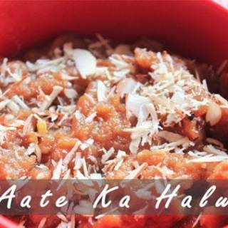 Aate ka halwa on a red bowl with almond and cashew