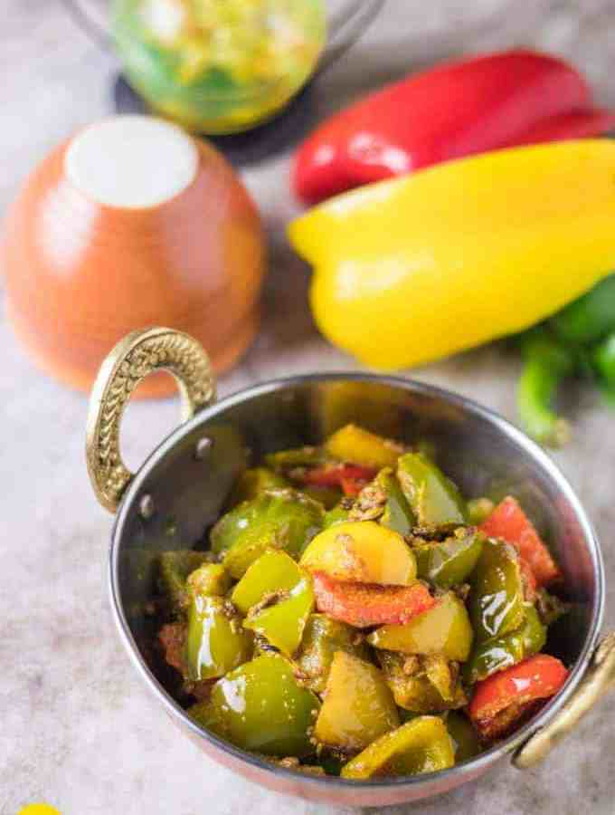 Achari shimla mirch on a deep vessel with some capsicum and bell pepper in the background with a clay pot kept on a white marble |