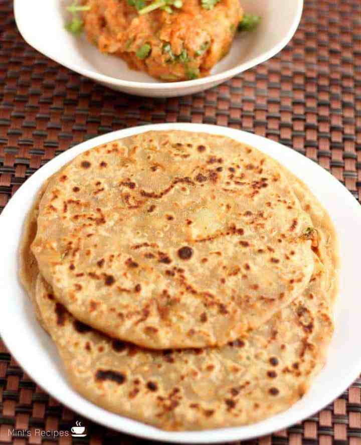Aloo Parantha | On a white plate with some aloo paratha's kept on a dark color mat and some potato mixture on a white bowl.