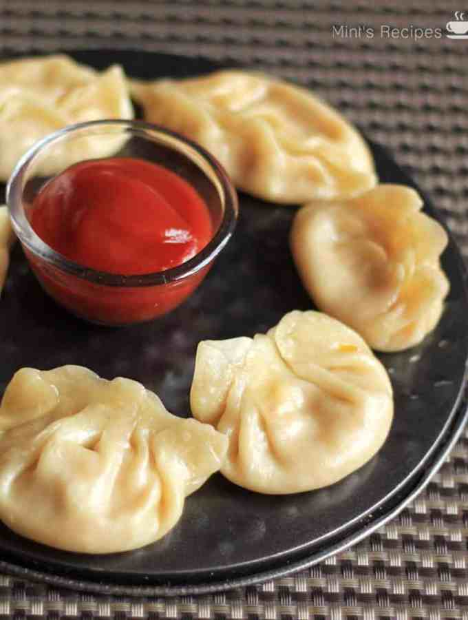 Cheese corn momo on a black round plate with some tomato sauce in the center putted on a dark coloured mat |