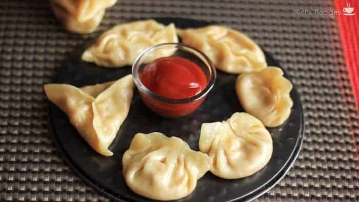 Veg momos on a white plate with some red chilli sauce in the center with a grey surface in background |