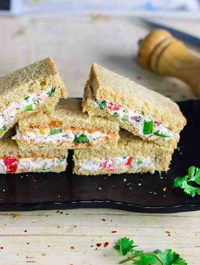 Cream Cheese Sandwich on a black plate for garnishing some coriander leaves and some chilli flakes|