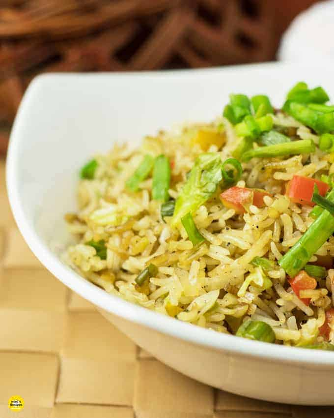 Vegetable fried rice on a white bowl garnish with spring onion on a mat with a dark background|