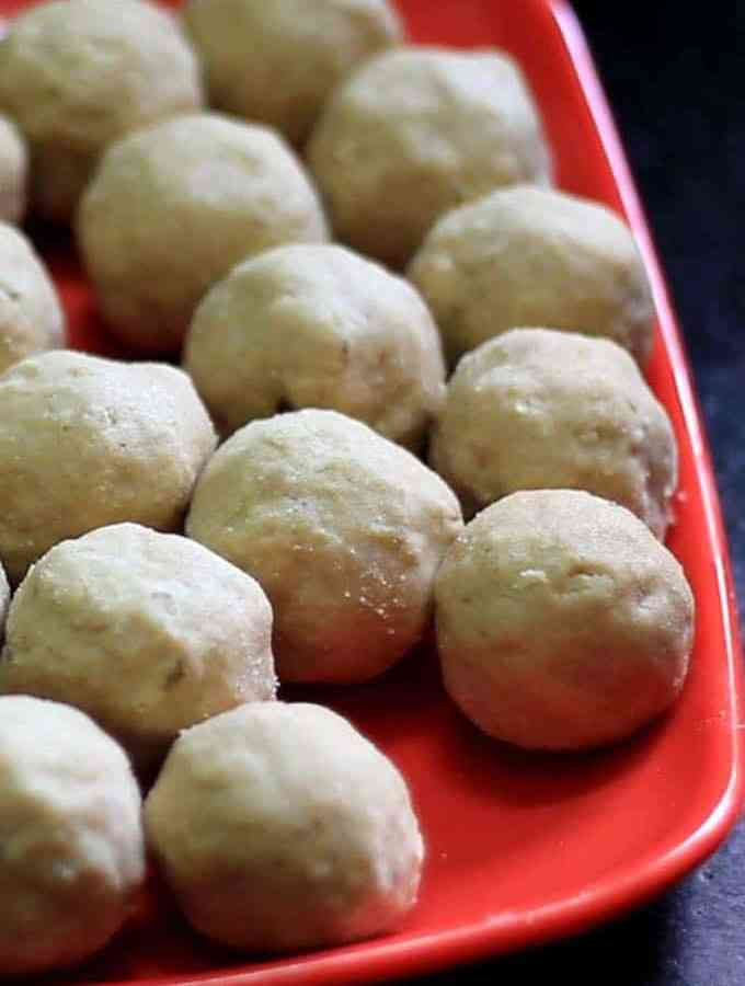 Gond-ke-laddu on a red plate with lots of pieces of laddu's on it with dark background |