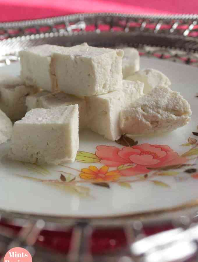 Paneer cutted into cubes on a silver coloured plate