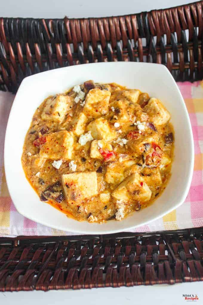 Khoya paneer in a deep vessel with some paneer crumbs on top for garnishing on a wooden surface with an handkerchief with a spoon l