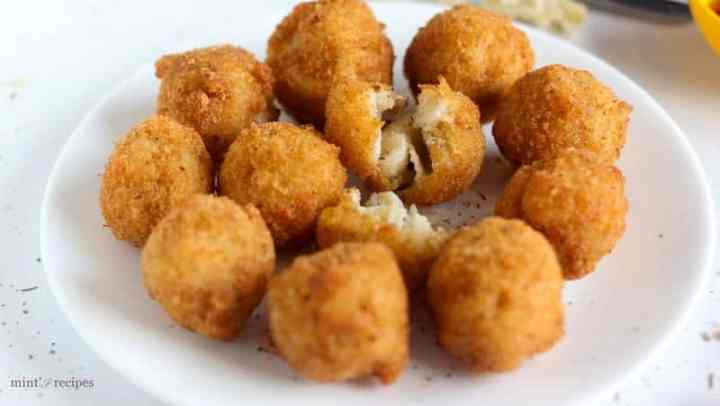 Macaroni cheese balls on a white plate with some black pepper sprinkles on it kept on a white surface |