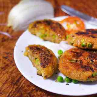 Veg Aloo Tikki on a white plate with some aloo tikki and garnished with some green peas kept on dark color paper surface