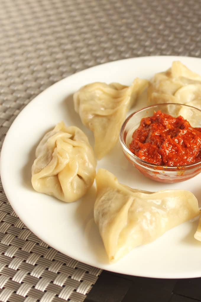 Veg momos on a white plate with some red chilli sauce