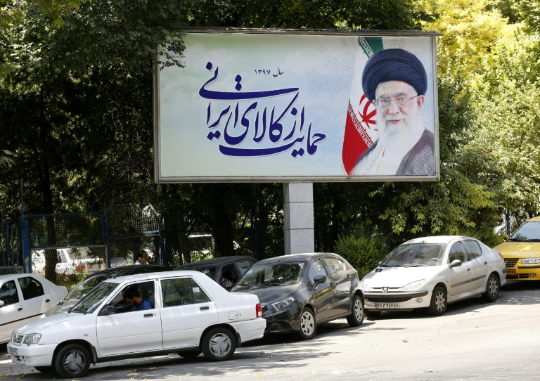 Cars drive by a poster depicting Iran's supreme leader Ayatollah Ali Khamenei in the capital Tehran on July 31, 2018