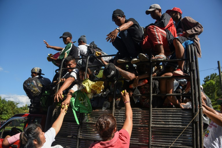 Honduran migrants traveling on a truck towards the US border receive food donations in the Mexican town of Acacoyagua, in Chiapas state