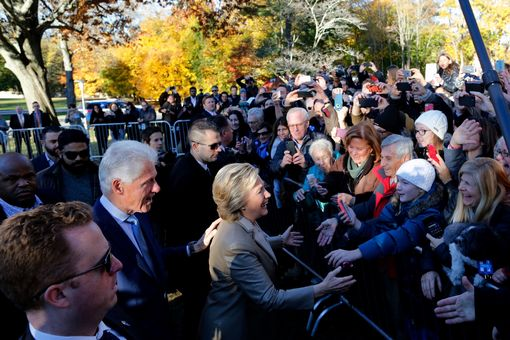 Democratic presidential nominee Hillary Clinton(C)and her husband Bill greet supporters after casting her vote in Chappaqua, New York