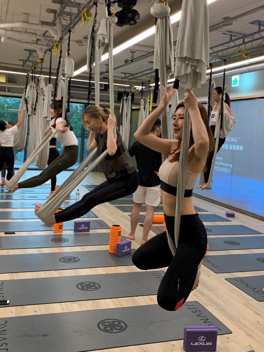 空中瑜珈運用懸垂的絹布和BARRE器材,藉助地心引力與布的螺旋力,以專注而有控制的肢體動作,並搭配正確的呼吸,進而提升身體的協調感,幫助身體深層的舒展與釋放緊繃壓力,達到心靈上的歇息。