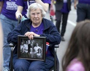 Lola Manoogian carries a photo of her husband an family as she and a crowd march up Guadalupe Street toward the Capitol in Austin, Tx., to commemorate and raise awareness about the 100th anniversary of the Armenian genocide in Turkey on Saturday, April 18, 2015. DEBORAH CANNON / AMERICAN-STATESMAN