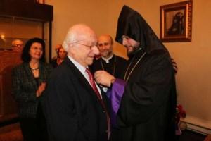 Dr. Arshavir Gundjian receives his medal from Archbishop Abgar Hovakimyan.