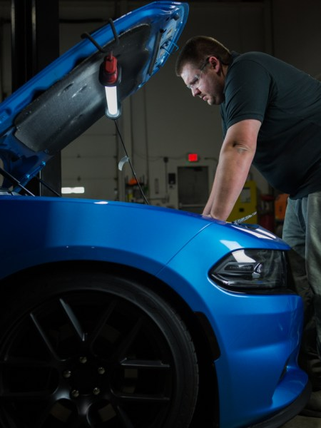 Our engineer, Dan, inspects the engine bay of our 2015 Charger R/T loaner for the best place to mount our catch can.