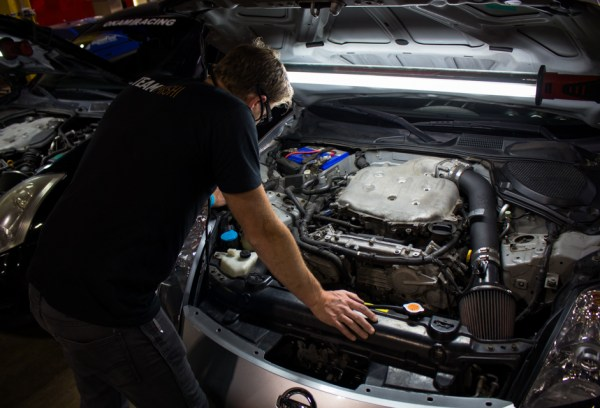 Jason inspects the engine bay of our loaner 350Z looking for the ideal location to mount our catch can.