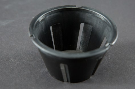 If you know anything about cyclone separators, this doesn't look like your traditional cyclone separator. We did run tests on a scaled-down version of the traditional baffle and found the best results came with a shortened baffle and bladed slots.