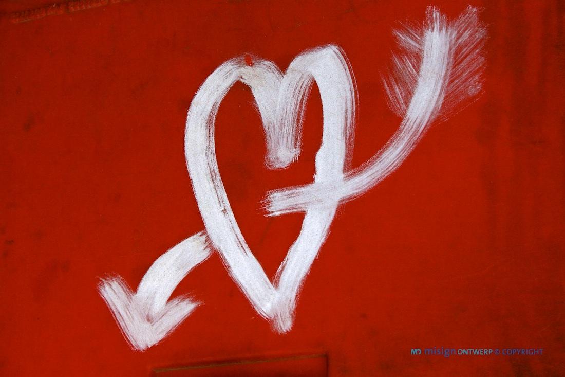 Rood hart met pijl grof op de muur geschilderd met witte verf