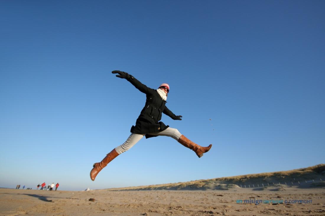 Vrouw springt in de lucht op het strand in Katwijk