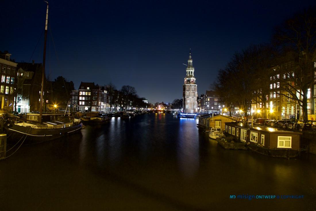 Avondopname van de Montelbaanstoren en woonboten aan de Oudeschans in Amsterdam