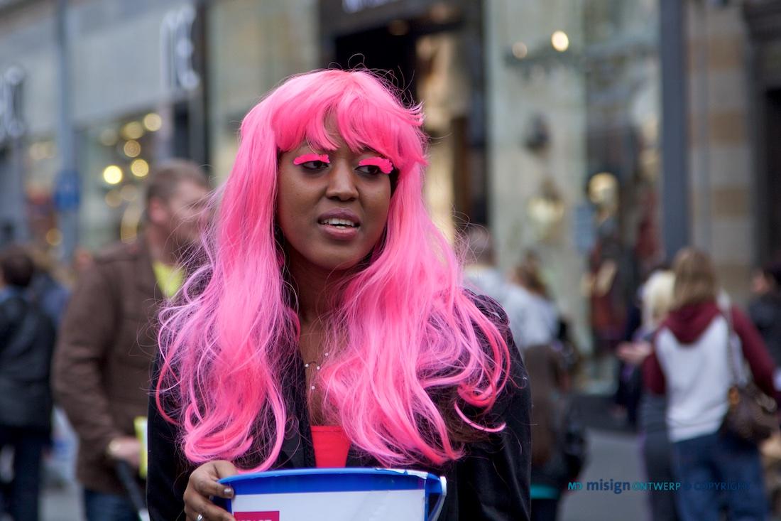 Donkere vrouw in Liverpool met roze pruik en roze wimpers en een collectebus in een winkelstraat.