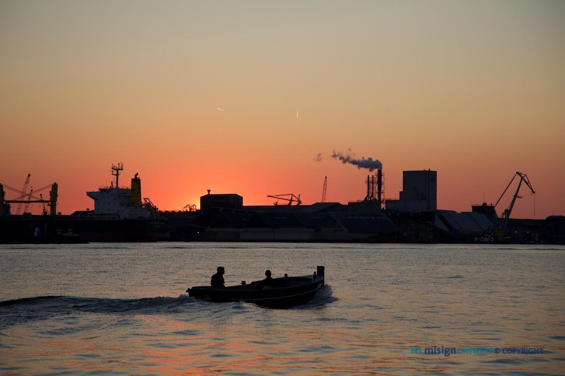 Sloep vaart over het IJ met zonsondergang in Amsterdam