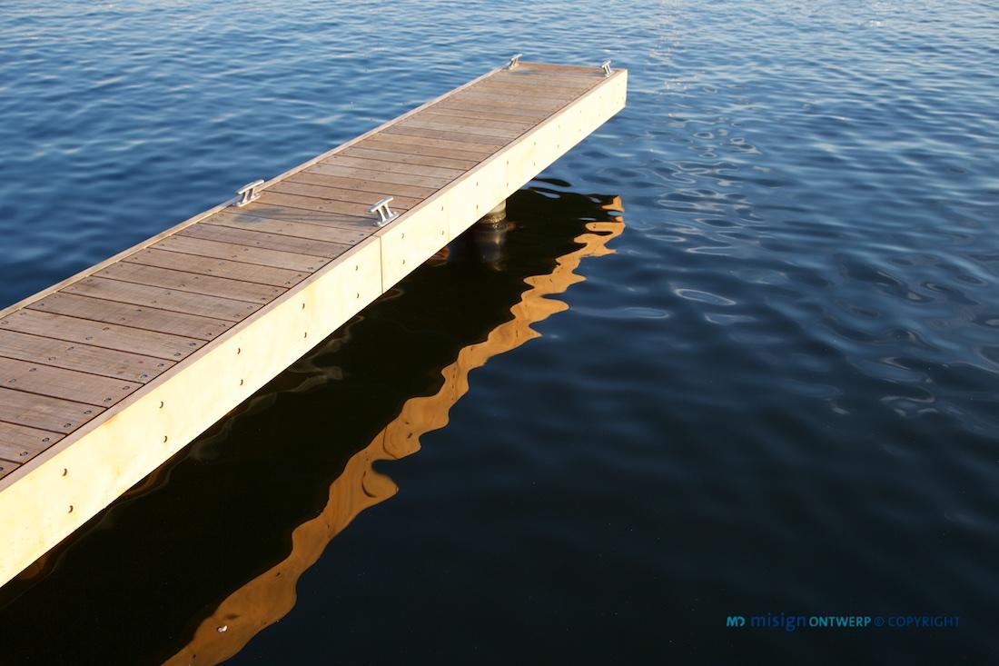 Houten aanleg stijger met reflectie op het blauw/zwarte water - misign ontwerp
