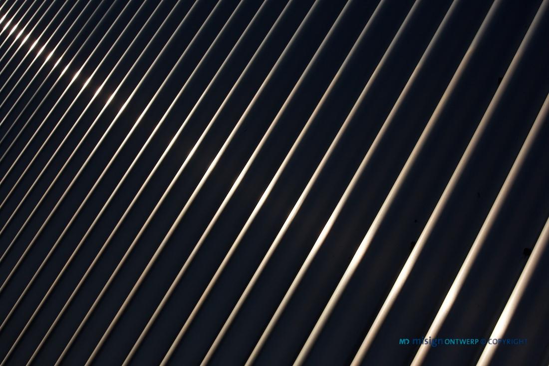 Lichtstraal reflectie op een golvende stalen wandplaat - misign ontwerp