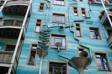 blaue hauswand mit kunstvoll platzierten Rohren und Trichtern in der Kunsthofpassage in Dresden