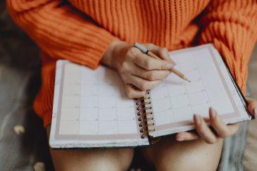 eine Frau im orangenen Pullover hält einen Block und einen Stift in der Hand