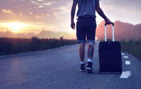 Ein Mann, der mit seinem Koffer dem Sonnenuntergang entgegenläuft