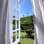 Window opening onto a green mountain in Sri Lanka