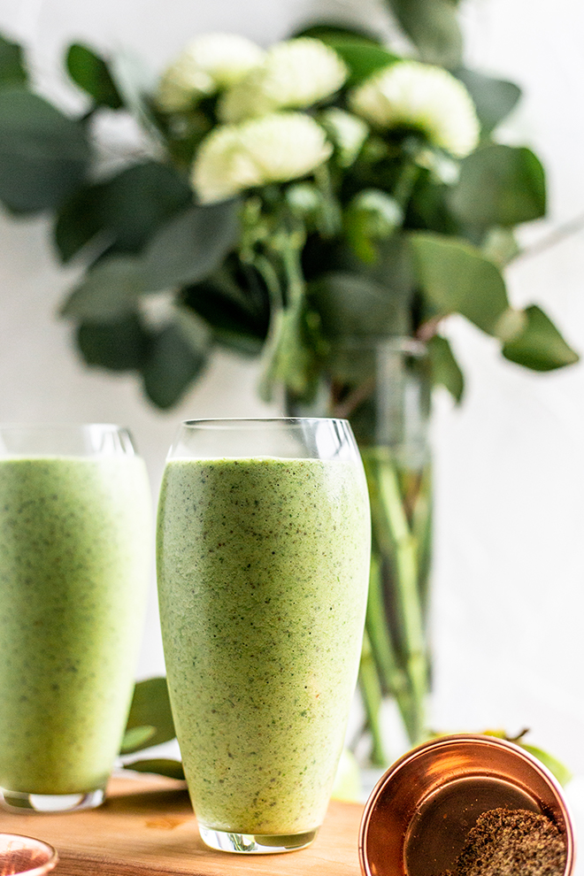 two green apple smoothies with a flower arrangements on a wood board with a white background
