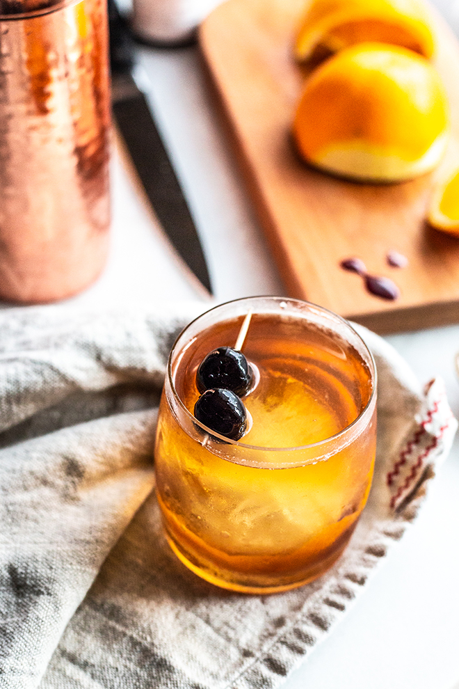 old fashioned cocktail with oranges and a copper shaker