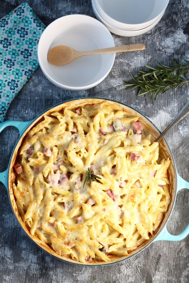 Baked Ham Penne Pasta Recipe in pan with serving bowls, napkin and fresh rosemary