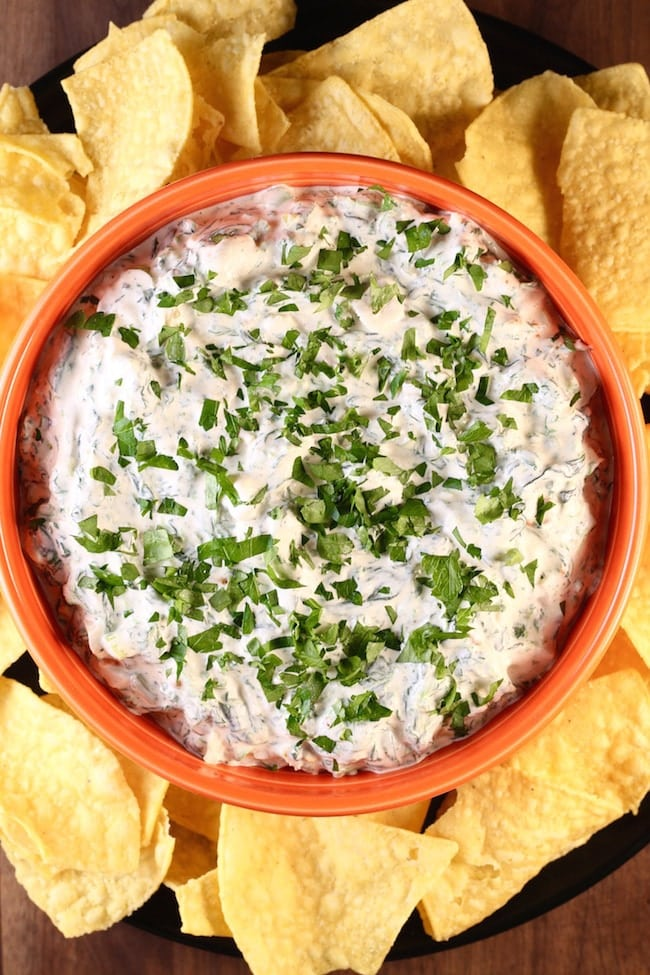 Knorr Spinach Dip in an orange bowl surrounded by tortilla chips