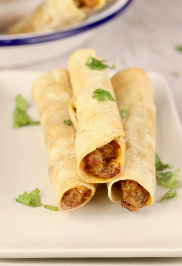 3 beef taquitos on a white plate