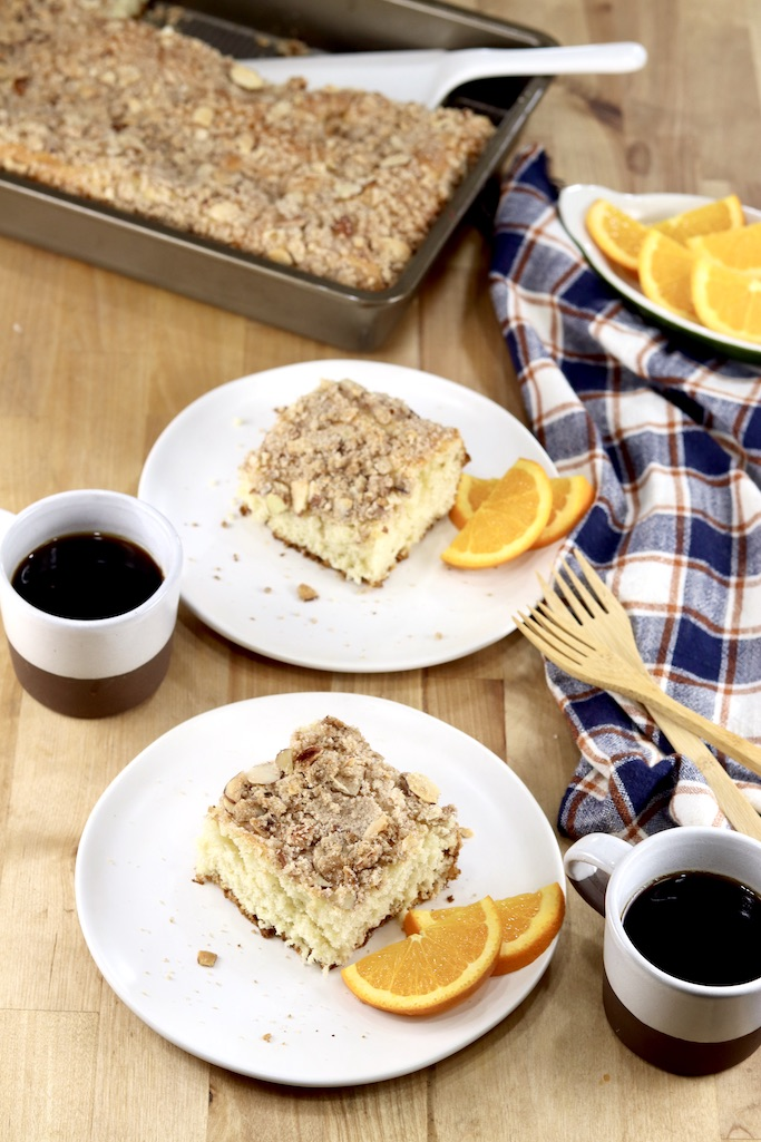 Almond Streusel Coffee Cake on 2 plates with coffee and sliced oranges