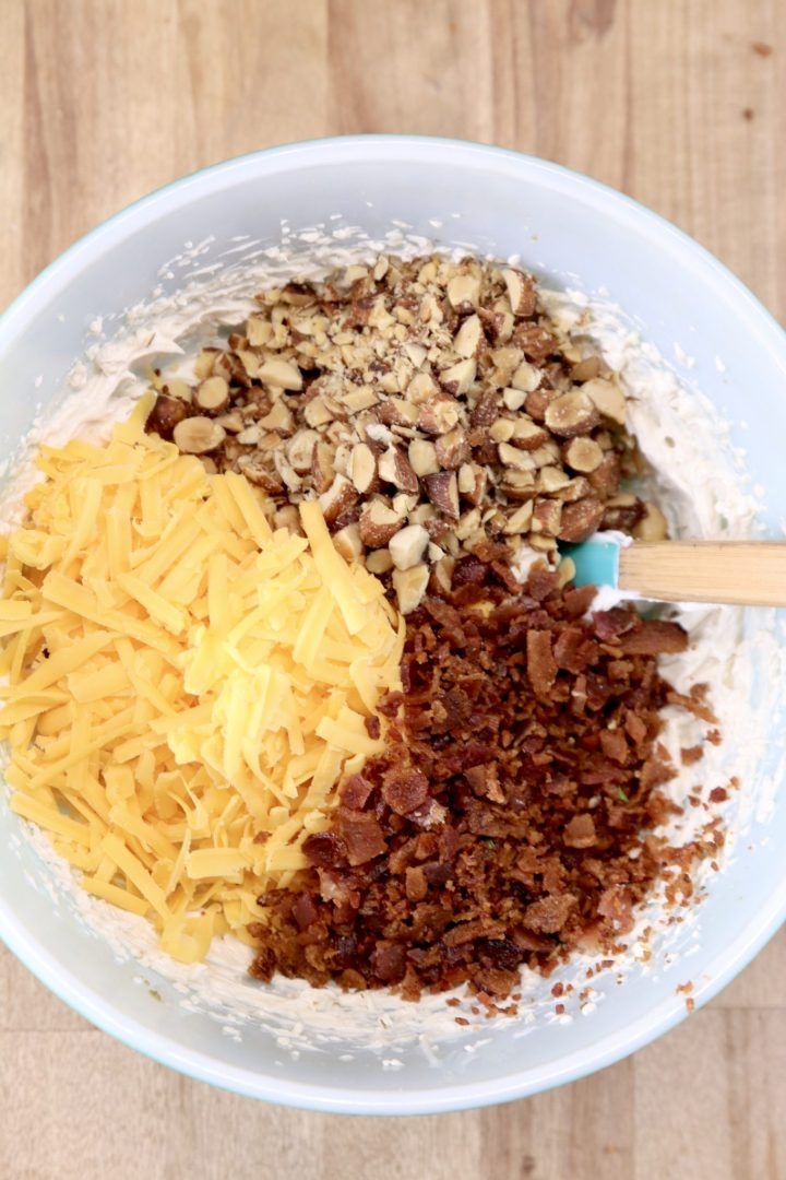 Bowl with crumbled bacon, shredded cheese and chopped almonds